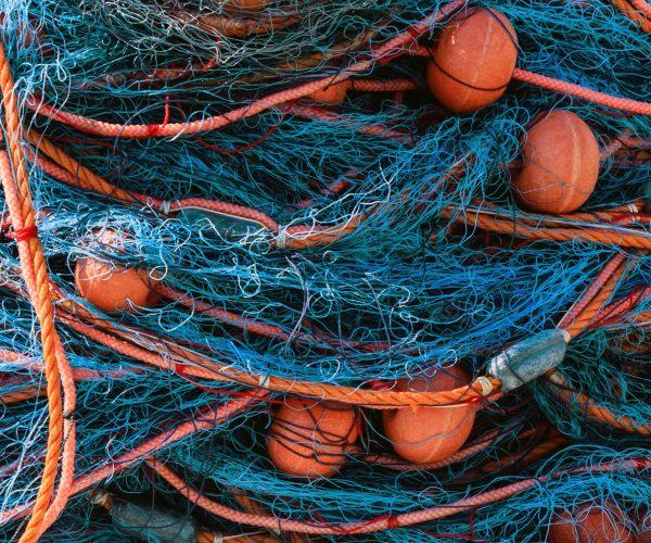 Stacks of fishing nets on blue sea water background. Marsaxlokk